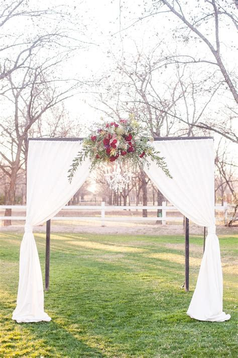 Romantic outdoor wedding ceremony arbor, ruby red flowers