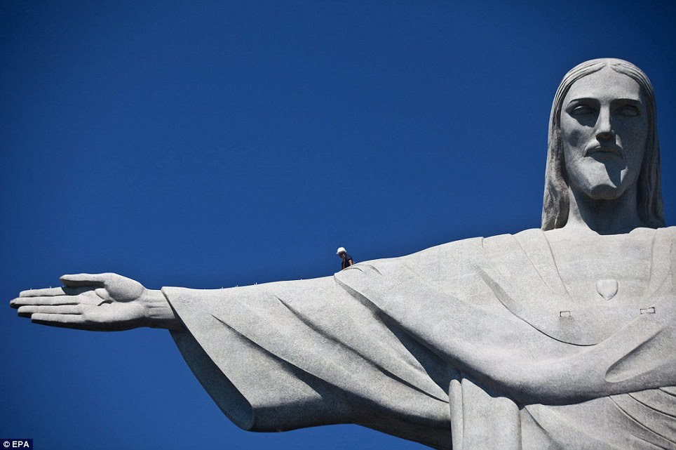 High-rise work: A construction worker walks on an arm of Christ the Redeemer statue in Rio de Janeiro to inspect damage after recent storms