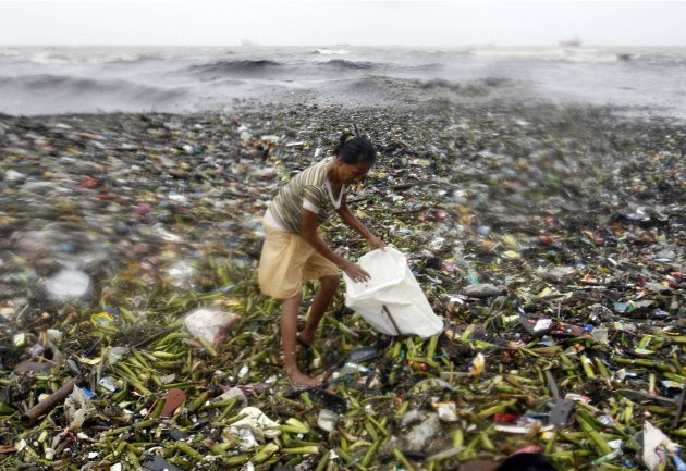 A woman balances on top of garbage at the height of Typhoon Nanmadol she collects recyclable materials along Manila Bay in Manila