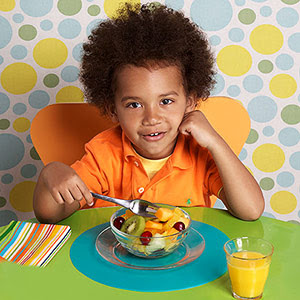 child eating fruit salad