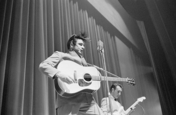 Johnny Cash and electric guitarist Luther Perkins perform on stage in White Plains, New York. Cash's hair flies up in the air crazily as he jams to the music, ca. 1959.