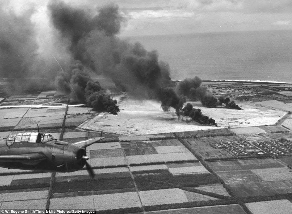 Aerial view: A Grumman TBF-1 Avenger flies over fields bombed by U.S. soldiers at Japanese-occupied Tinian Island, Northern Mariana Islands, on June 30, 1944