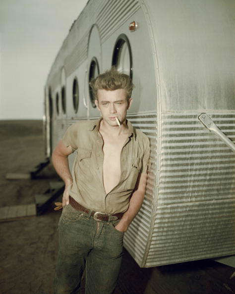 circa 1955:  American actor James Dean (1931 - 1955) leaning against a dressing room trailer with his shirt open to the waist while smoking a cigarette on the set of director George Stevens's film, 'Giant,' in which he starred.  (Photo by Hulton Archive/Getty Images)