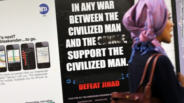 A woman walks by a controversial ad in a New York subway station last fall. The word