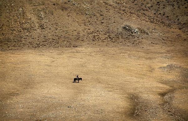 A herder rides a horse on grasslands located southwest of the Mongolian capital city Ulan Bator, April 4, 2012. REUTERS-David Gray