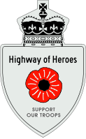A Highway of Heroes reassurance marker with a red poppy flower in place of a number. Above that is the text Highway of Heroes, and below it SUPPORT OUR TROOPS.