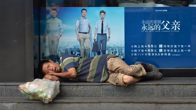 Un homme qui ramasse les ordures fait une pause devant une boutique de vêtements, à Hefei, dans la province d'Anhui, en Chine.
