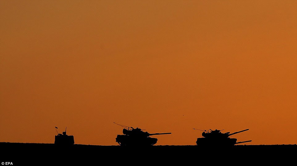 Turkish tanks are silhouetted against the orange sky near the Turkey-Syria border after mortar shells hit Turkish territory in Suruc district, near Sanliurfa