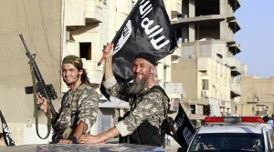 Militant Islamist fighters wave flags as they take part in a military parade along the streets of Syria's northern Raqqa province