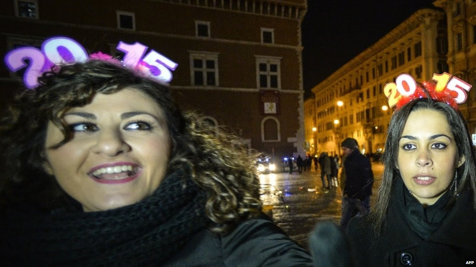 People cheer on the Piazza Venezia to celebrate the new year in Rome (01 January 2015)