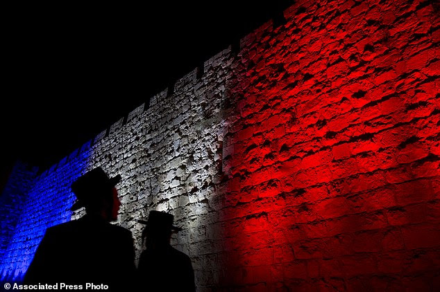 Jews look at Jerusalem's Old City walls illuminated by the colors of the French national flag in solidarity with France after attacks in Paris, in Jerusalem. Jewish people are fleeing western Europe for Israel due to attacks