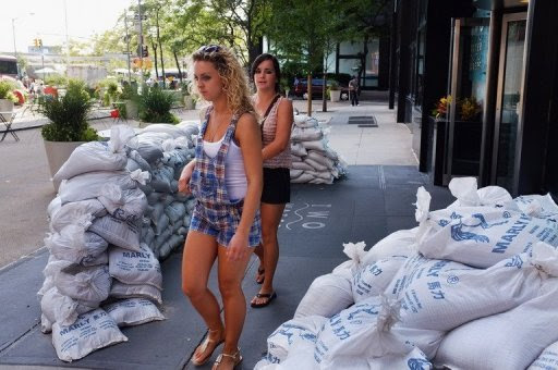 Two women walk by remaining sandbags in front of a hotel in lower Manhattan a day after Hurricane Irene