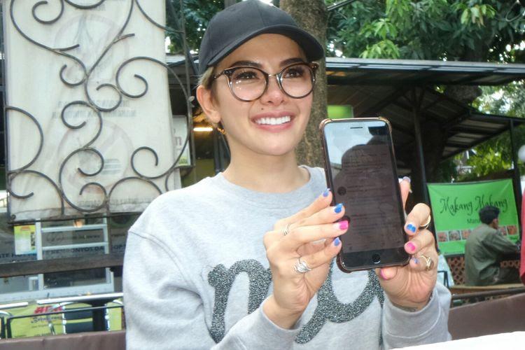 Artis peran Nikita Mirzani menunjukkan akun Twitter miliknya dalam jumpa pers di Food Garden, Kemang, Jakarta Selatan, Rabu (4/9/2017).