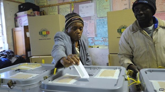 An 80-year-old Zimbabwean casts her vote in a polling station in a pass cart in Harare on 31 July 2013