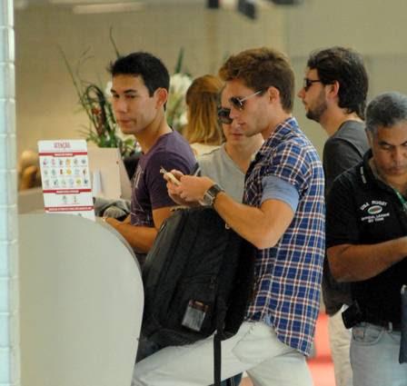 De óculos escuros e sozinho, Jonatas Faro não foi reconhecido na fila do embarque