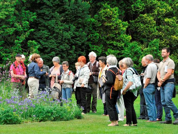 groep bezoekers met een gids bij enkele bloeiende planten