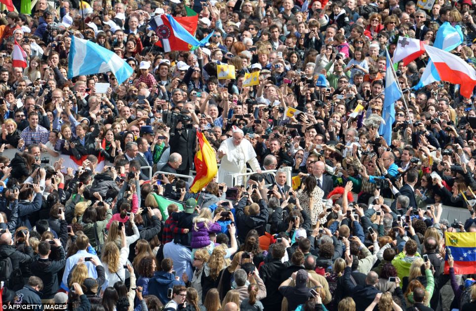 Crowds: Pope Francis (centre) waves to the crowd from the Popemobile in St Peter's Square today