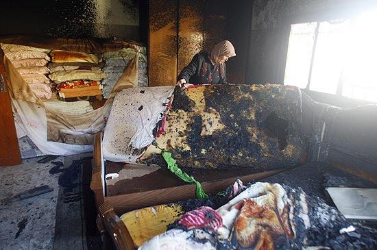 palestina segura um colchão incendiado em meio a destruição causada por colonos israelenses em Hiwwara
