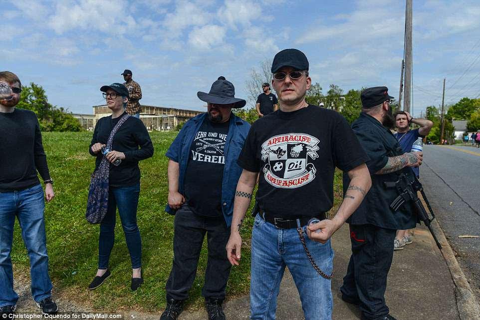 Antifa se posa antes del mitin, incluye a un hombre (de pie a la derecha) portando abiertamente un rifle estilo AR-15