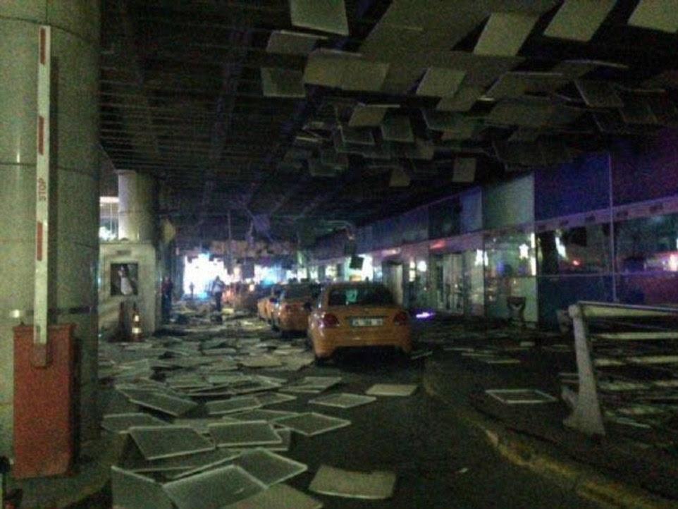 telhas do teto espalhados pelo chão fora do terminal de chegadas internacionais, que foi atingida por três explosões suicidas na terça-feira