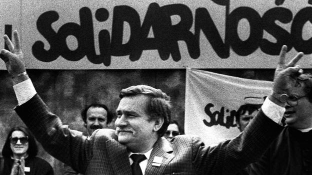 Solidarity founding leader Lech Walesa shows v-sign in front of Solidarity poster during his presidential campaign in Plock (7 May 1989)