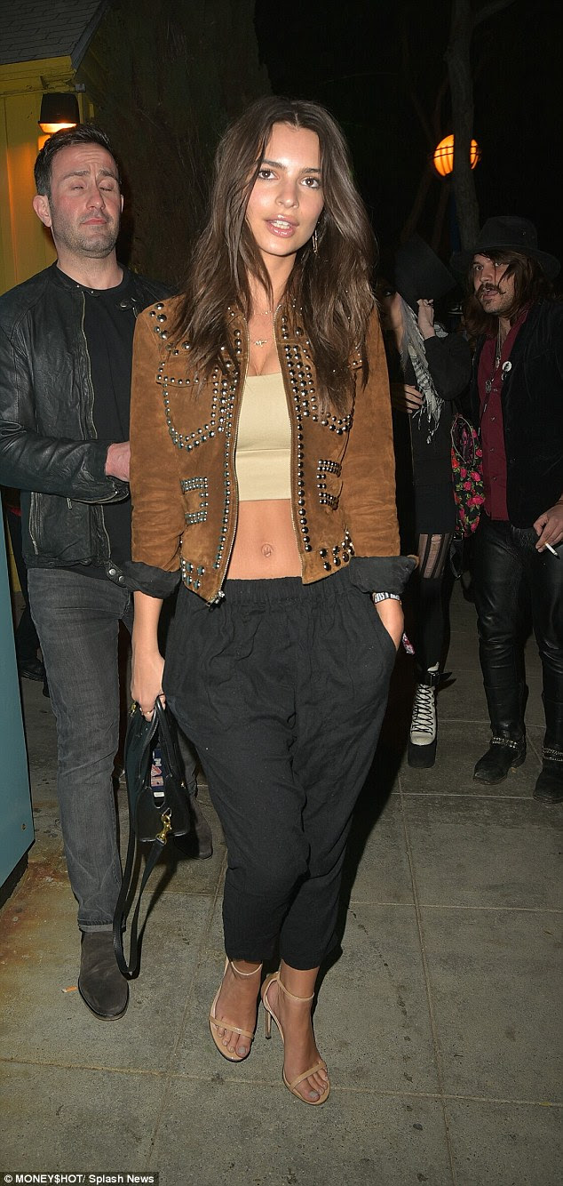 Model moment:Emily Ratajkowksishowcased her enviably taut abs and ample assets in a nude bandeau top and relaxed black joggers as she led the celebrity arrivals at the Troubadour in West Hollywood for the Guns N' Roses reunion gig