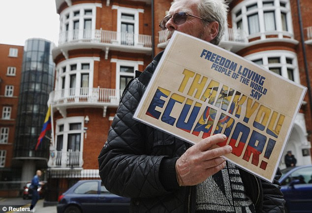 A supporter of Edward Snowden holds a sign that reads