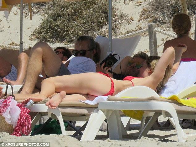 Olhando para trás: O casal feliz refletia sobre fotos juntos, enquanto estavam deitados em suas espreguiçadeiras