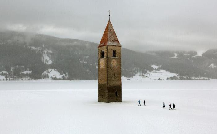 Колокольня старой церкви, торчащая из вод замерзшего озера.