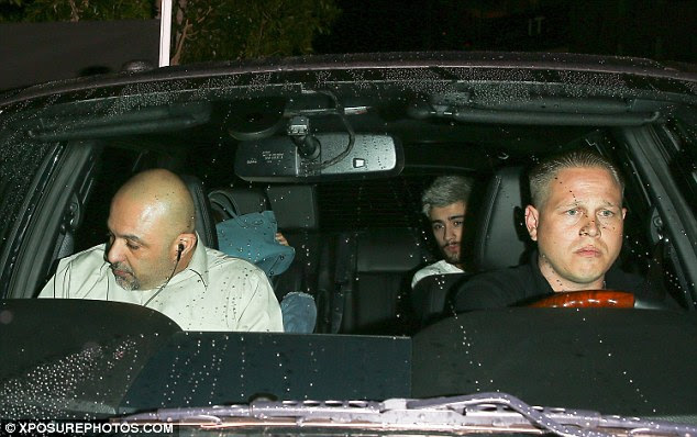 Why so shy? The new couple sat in the back of the car with Gigi hiding her face behind her blue leather designer handbag