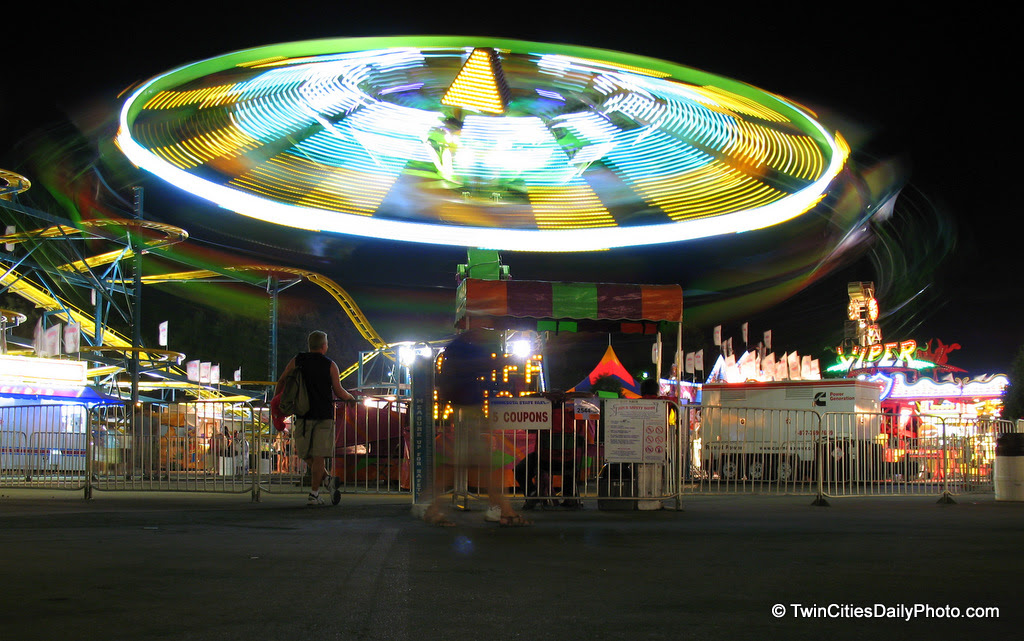 The magic of lights in motion out in the Midway at the Minnesota State Fair. I believe the ride is called 'Cliff Hanger'. You lay on a metal frame, similar to superman flying .