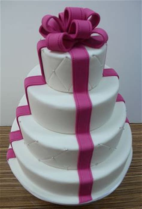 Four tier round wedding cake with fuschia bow