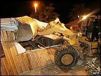 A Palestinian bulldozer tears down a shop on Gaza City's beach road