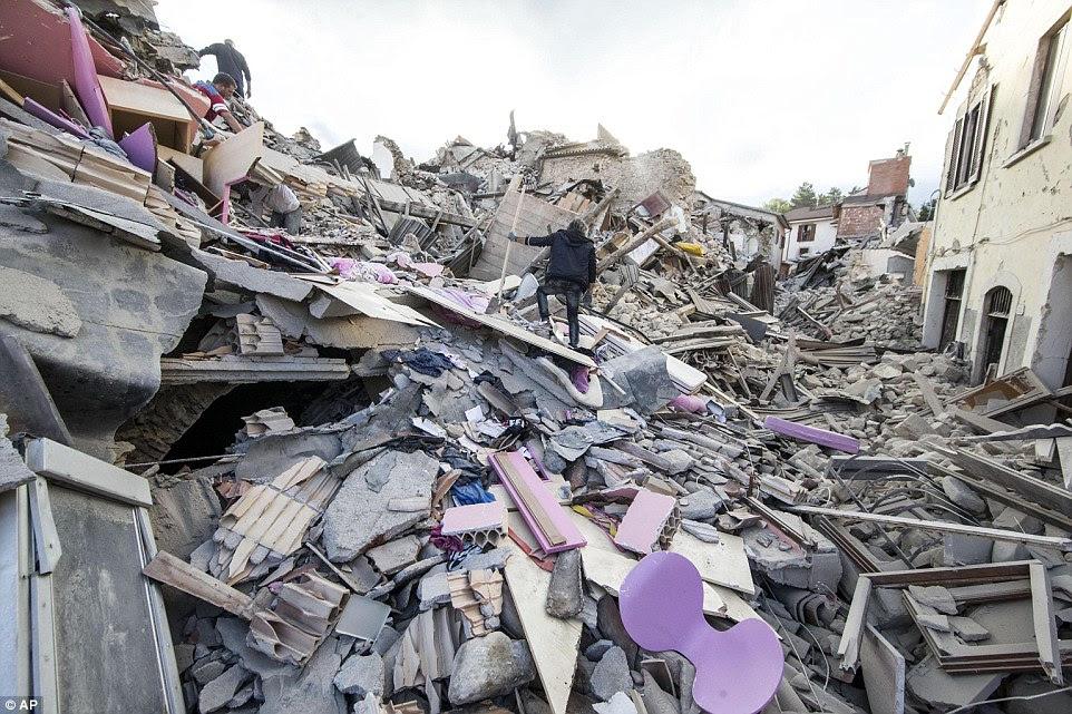 Virado do avesso: A decoração roxa da casa de uma família é visto entre os escombros cinza como as pessoas procuram por sinais de vida em Amatrice