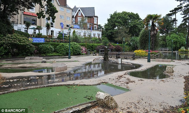 Underwater golf: A crazy golf course in Bournemouth begins to reappear as floodwater drains away
