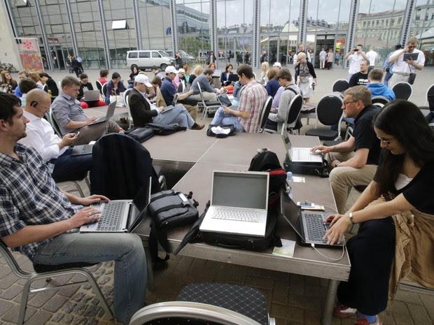 """Pessoas usam seus notebooks ao ar livre durante o evento """"Working Everywhere"""" (""""trabalhando em todos os lugares"""", na tradução livre) nesta sexta-feira (31), em Riga, capital da Letônia. (Foto: Ints Kalnins/Reuters)"""