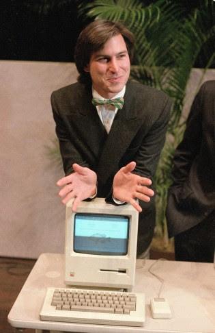 "Steve Jobs leans on the new ""Macintosh"" personal computer following a shareholder's meeting on January 24, 1984. Photo: Paul Sakuma/AP"