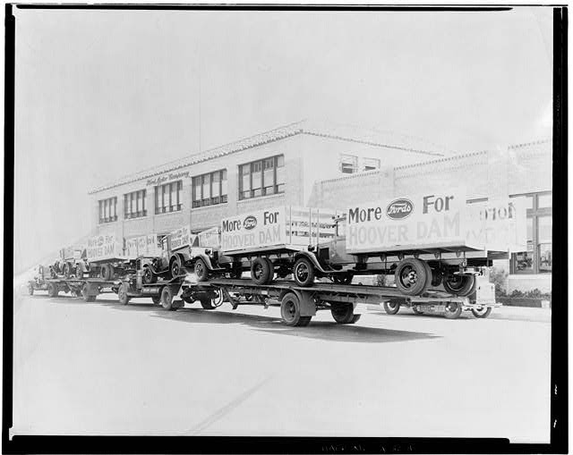 94.  Neg. No. F-130, Sep 24, 1931, EXTERIOR-OFFICE BUILDING AND ASSEMBLY BUILDING, WEST SIDE, SHOWING TRUCKS AND TRAILORS LOADED WITH NEW TRUCKS DISPLAYING SIGNS 'MORE FORDS FOR HOOVER DAM' - Ford Motor Company Long Beach Assembly Plant, Assembly Building, 700 Henry Ford Avenue, Long Beach, Los Angeles County, CA
