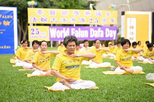 '图2~3:二零一七年五月二日,新加坡法轮功学员在芳邻公园庆祝即将来临的世界法轮大法日。图为学员们正在集体炼功。'