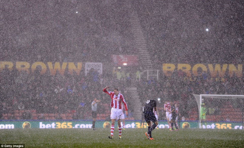 Take cover! Peter Crouch of Stoke City reacts as heavy rain falls and play is halted during his side's Capital One Cup Quarter Final match against Manchester United