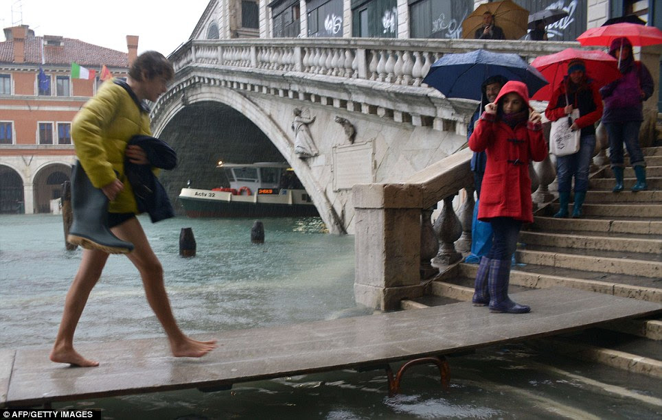 One tourist takes off their boots to walk on a makeshift footbridge in the rain