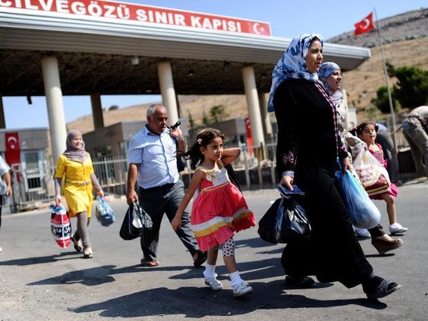30/8 - Famílias sírias cruzam a fronteira e entram na Turquia pela passagem de Cilvegozu para se refugiar no país vizinho, com medo da tensão internacional que torna iminente um conflito com os EUA (Foto: Bulent Kilic/AFP)
