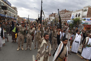 Shiite rebels, known as Houthis, hold up their weapons…