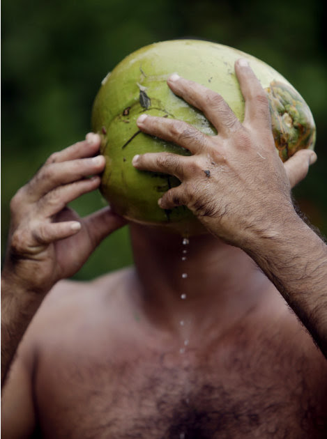 """In this photo taken Wednesday Aug. 24, 2011, Yoandri Hernandez Garrido, 37, known as """"Twenty-Four,"""" drinks juice from a coconut in Baracoa, Guantanamo province, Cuba.  Hernandez is proud of his extra"""