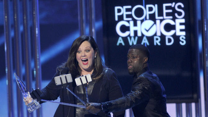 Kevin Hart, right, films Melissa McCarthy as she accepts the award for favorite comedic movie actress at the People's Choice Awards at the Nokia Theatre on Wednesday, Jan. 7, 2015, in Los Angeles. (Photo by Chris Pizzello/Invision/AP)