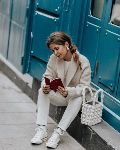 Uno de los últimos looks en converse de bota, en un estilismo en blancocon el bolso que marca tendencia este año.