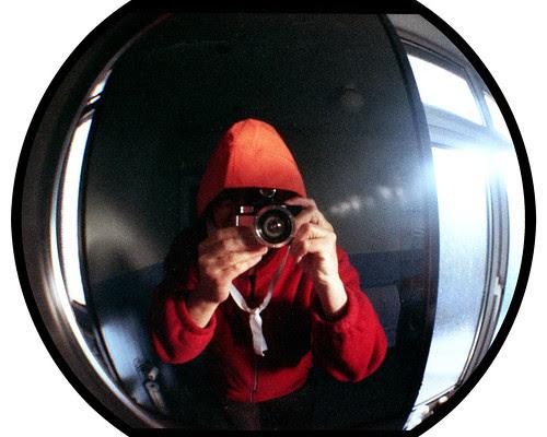 reflected self-portrait with Lomo Fisheye 2 camera and orange sou'wester by pho-Tony