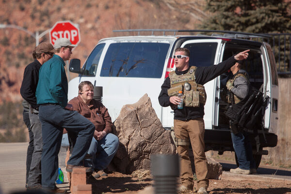 Law enforcement officers investigate in Hildale, Utah, Tuesday. Several top leaders from Warren Jeffs' polygamous sect were arrested Tuesday on federal accusations of food stamp fraud and money laundering marking one of the biggest crackdowns on the group in years.