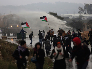 Protesters run as an Israeli Army truck fires a water cannon, containing a foul-smelling substance, during clashes with stone-throwing protesters in the West Bank village of Nabi Saleh, near Ramallah (Reuters / STR)