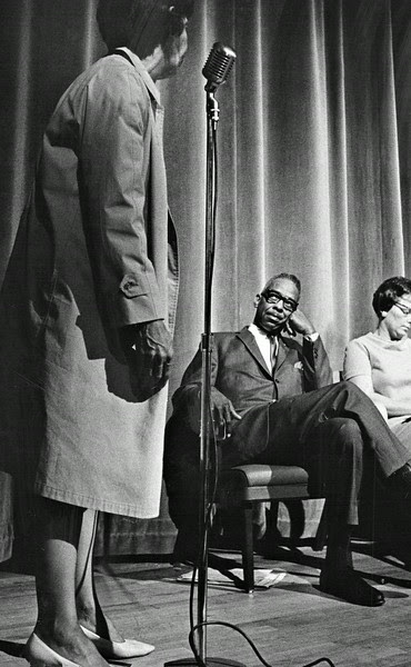 Description of  MAY 9 1968 - Warren Alexander, assistant director of Colorado Civil Rights Commission, and Mrs. Dorothy Wham, chairman of Southeast Denver School Action Committee, listen to an unidentified woman attack a proposal. (Steve Larson/The Denver Post)